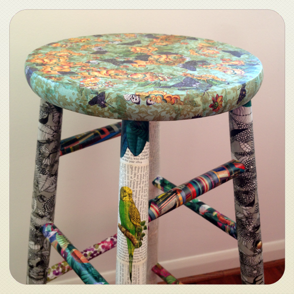 wooden stool decoupaged with an assortment of papers applied in layers