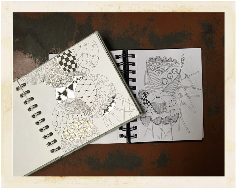 2 open sketchbooks showing geometric drawings